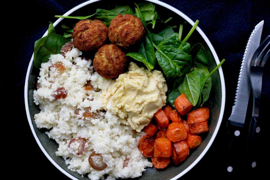 Billede af fyldig salat med blomkålscouscous, bagte gulerødder og hummus