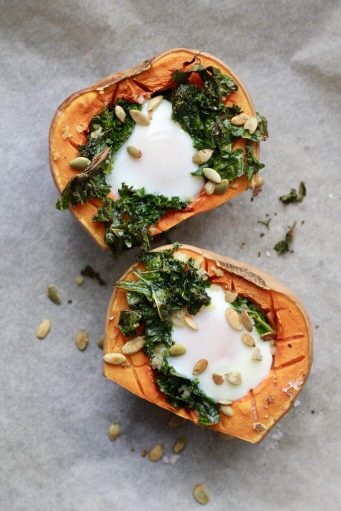 Bagt butternut squash med grønkål, bulgur og æg 2 personer Ingredienser: 1 butternut squash (kun den tykke ende med kerner) 1 håndfuld grønkål 2 æg Salt og peber 40 bulgur, kogt 1 spsk græskarkerner, ristede Fremgangsmåde: 1. Tænd ovnen på 180 grader, varmluft. 2. Skær butternut squashen over cirka på midten, så du ender med den nederste del med kerner. Halverer den og fjern kernerne. 3. Skær riller ned i squash-kødet, men ikke helt igennem. Skær evt. også lidt af bunden, så den står mere stabilt, på en bageplade beklædt med bagepapir. 4. Kom salt og peber på og bag dem i ovnen ca. 20-30 min. (afhængig af størrelsen) til de er næsten møre. 5. Kog bulgur, hvis du ikke har kogt den. 6. Ordne grønkål i mindre stykker og steg det hårdt af på panden i lidt olie. Krydr med salt og peber og bland med det kogte bulgur. 7. Kom det i bunden af de forbagte butternuts squash og hæld derefter ægget ned i hullet. Det kan være en hjælp evt. at slå ægget ud i en lille skål først, så det er nemmere at styre, når det skal ned i hullet. 8. Bag butternut shuashene videre i ca. 10-12 min, til æggene er færdige men stadig har en flydende blomme. 9. Top med ristede græskarkerner.