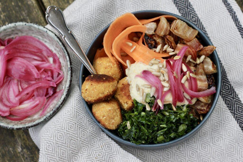 Poke bowl med bagte bolchebeder, gulerodsbånd, frisk grønkål, ærte-falafels, ristede solsikkekerne og Ingrid-ærte-hummus